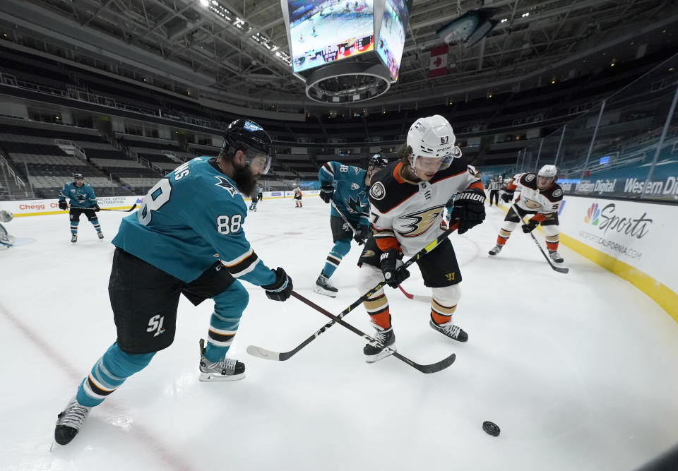 San Jose Sharks defenseman Brent Burns (88) works for the puck along the boards against Anaheim Ducks center Rickard Rakell (67) during the second period of an NHL hockey game Wednesday, April 14, 2021, in San Jose, Calif. (AP Photo/Tony Avelar)