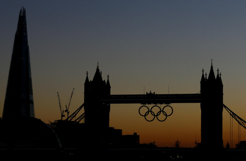 Tower Bridge with Olympic rings is silhouetted as the sun sets in London, Monday, July 23, 2012. The summer Olympics in London will start on Friday July 27. (AP Photo/Kirsty Wigglesworth)