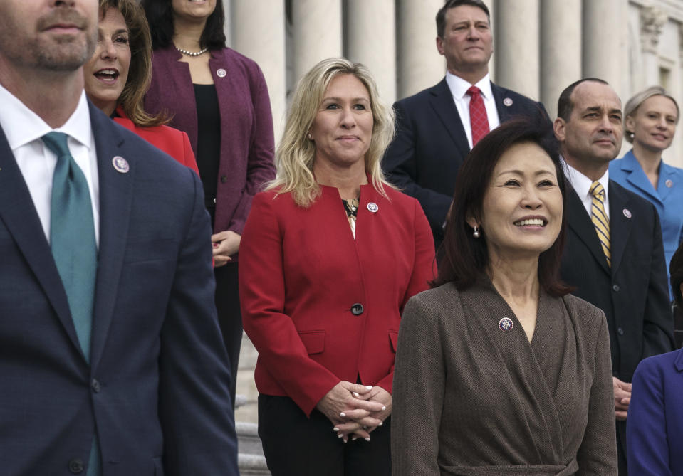 """In this Jan. 4, 2021, photo, Rep. Marjorie Taylor Greene, R-Ga., center, stands with other GOP freshmen during an event at the Capitol in Washington. Republican Senate leader Mitch McConnell is calling the far-right Georgia Republican's embrace of conspiracy theories and """"loony lies"""" a """"cancer for the Republican Party."""" House Democrats are mounting an effort to formally rebuke Greene, who has a history of making racist remarks, promoting conspiracy theories and endorsing violence directed at Democrats. (AP Photo/J. Scott Applewhite)"""