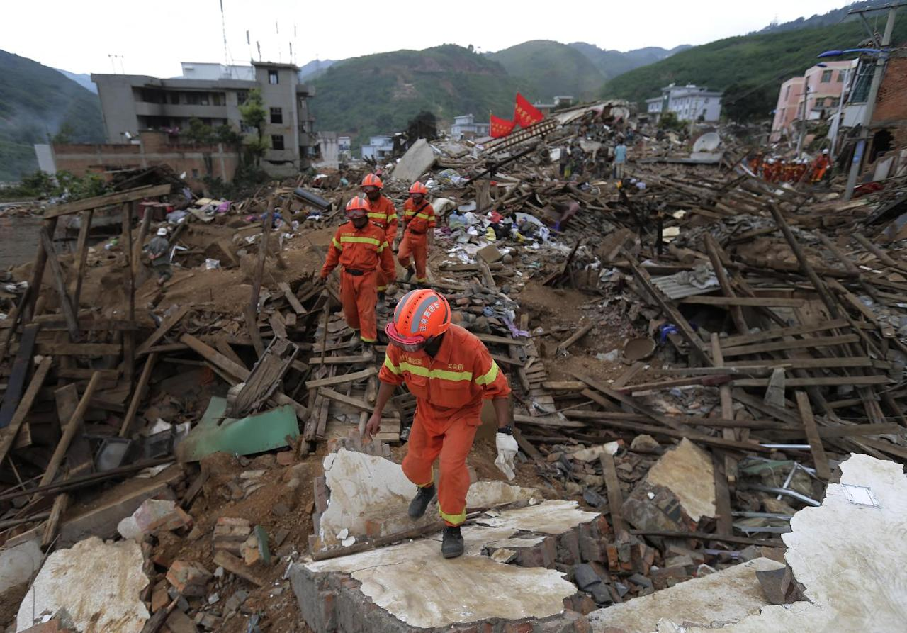 Rescuers walk through rubbles from destroyed houses as they search for survivors following a massive earthquake in the town of Longtoushan in Ludian County in southwest China's Yunnan Province Tuesday, Aug. 5, 2014. Rescuers raced Tuesday to evacuate villages near rising lakes formed by landslides, complicating relief efforts following a strong earthquake in southern China that killed more than 300 people and has left thousands homeless. (AP Photo/Andy Wong)