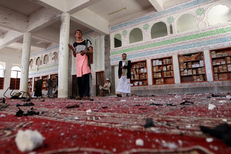 Yemeni armed men inspect the damage following a bomb explosion at the Badr mosque in southern Sanaa on March 20, 2015 (AFP Photo/Mohammed Huwais)