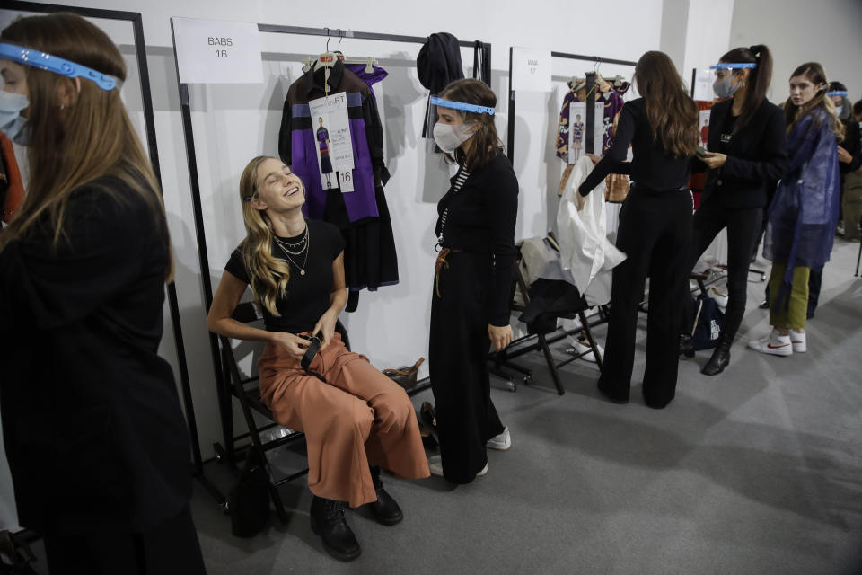 Models get ready in the backstage prior to the start of the Shi.RT women's Spring-Summer 2021 fashion show, in Milan, Italy, Sunday, Sept. 27, 2020. (AP Photo/Luca Bruno).