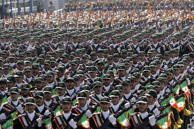 FILE - In this Friday, Sept. 21, 2012 file photo, Iran's Revolutionary Guard troops march during a military parade commemorating the start of the Iraq-Iran war 32 years ago, in front of the mausoleum of the late revolutionary leader Ayatollah Khomeini, just outside Tehran, Iran. Even before Iran's envoys could pack their bags in Geneva after wrapping up a first-step nuclear deal with world powers, President Hassan Rouhani was opening a potentially tougher diplomatic front: Selling the give-and-take to his country's powerful interests led by the Revolutionary Guard. Whether Iran's hard-liners will aid or obstruct expanded UN inspections and other points of the accord stands as the biggest wild card on whether it can hit it marks and test Iran's claims that it does not seek nuclear weapons. (AP Photo/Vahid Salemi)