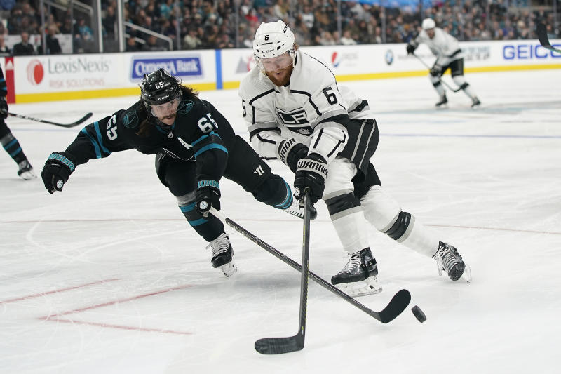 San Jose Sharks defenseman Erik Karlsson (65) pokes the puck away from Los Angeles Kings defenseman Joakim Ryan (6) during the second period of an NHL hockey game in San Jose, Calif., Friday, Dec. 27, 2019. (AP Photo/Tony Avelar)