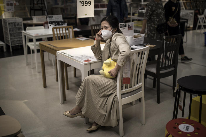 Customers wear protective masks while her make call on chair at an IKEA store on April 25, 2020 in Wuhan, China. IKEA Wuhan Branch resumed business on April 21.the government started lifting outbound travel restrictions on April 8 from Wednesday after almost 11 weeks of lockdown to stem the spread of COVID-19. (Photo by Getty Images)