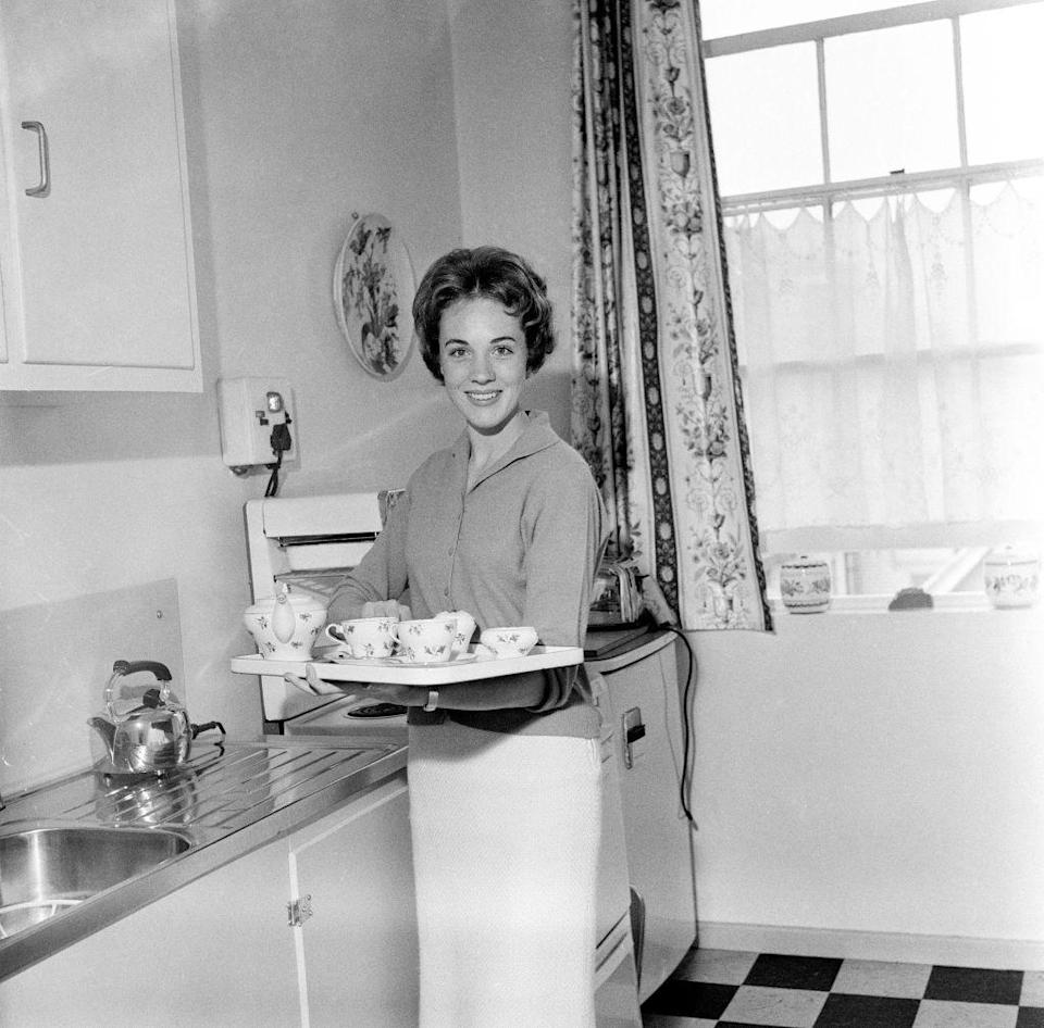 <p>The <em>Mary Poppins </em>star looks polished as she poses in the kitchen of her London apartment with a tea set in 1959.  </p>
