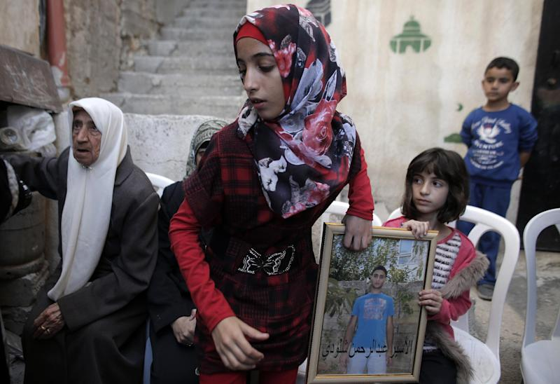The sisters of Palestinian Abdelrahman Shaludi (C), who killed a baby and injured six others in Jerusalem after he rammed his vehicle into pedestrians, hold his portrait at their home in the east Jerusalem neighbourhood of Silwan on October 23, 2014