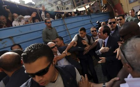 Presidential candidate and former army chief Abdel Fattah al-Sisi (R) gestures to his supporters as he arrives with his bodyguards at a polling station to cast his vote during the presidential election in Cairo May 26, 2014. REUTERS/Amr Abdallah Dalsh