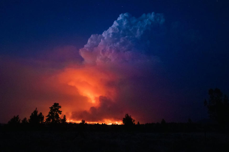 In this photo provided by the Oregon Office of State Fire Marshall, flames and smoke rise from the Bootleg fire in southern Oregon on Wednesday, July 14, 2021. The largest fire in the U.S. on Wednesday was burning in southern Oregon, to the northeast of the wildfire that ravaged a tribal community less than a year ago. The lightning-caused Bootleg fire was encroaching on the traditional territory of the Klamath Tribes, which still have treaty rights to hunt and fish on the land, and sending huge, churning plumes of smoke into the sky visible for miles. (John Hendricks/Oregon Office of State Fire Marshal via AP)