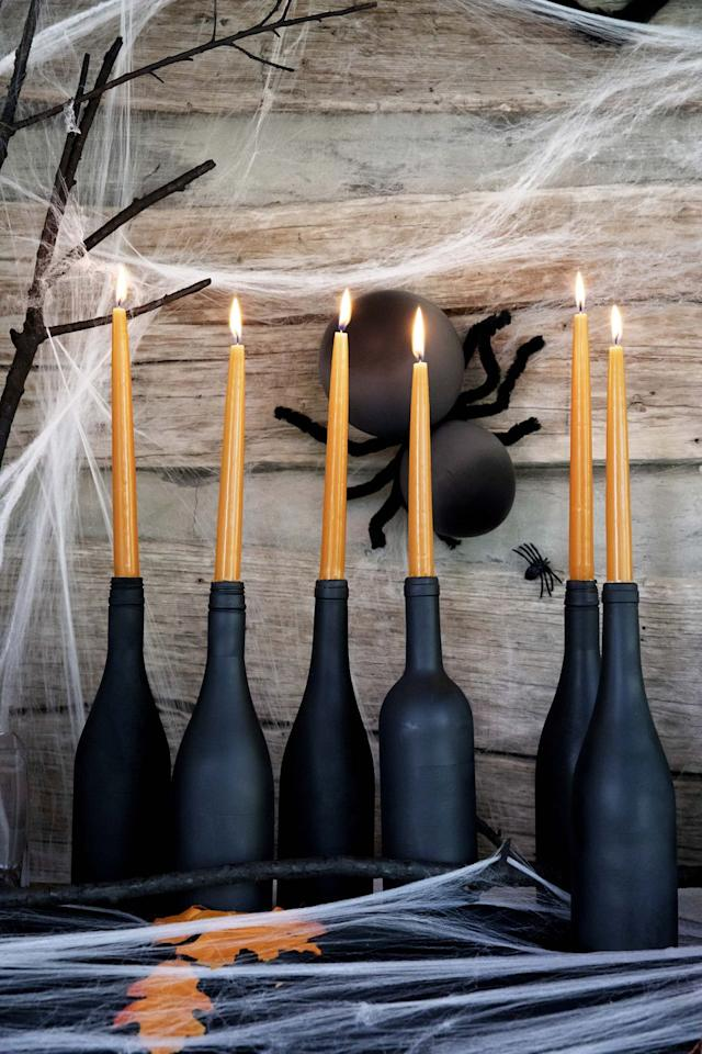 <p>Line up a set of eerie candles along the table for a spooky scene. Paint wine bottles with matte-black spray paint. Once dry, insert an orange taper candle in each opening. (Remember to keep candles away from anything flammable, and never burn unattended.)</p>