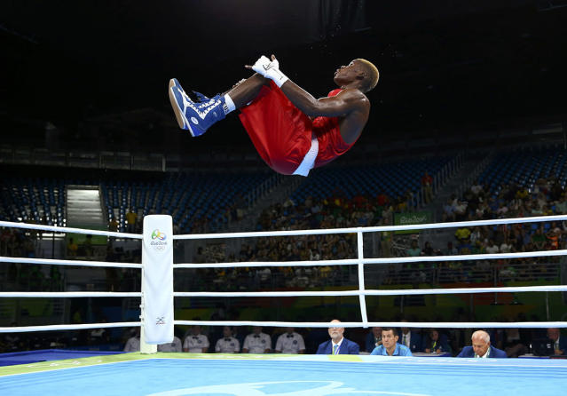 <p>Dieudonne Wilfred Seyi Ntsengue of Cameroon performs a somersault after winning his bout in men's middle (75kg) boxing on August 9, 2016. (REUTERS/Peter Cziborra) </p>
