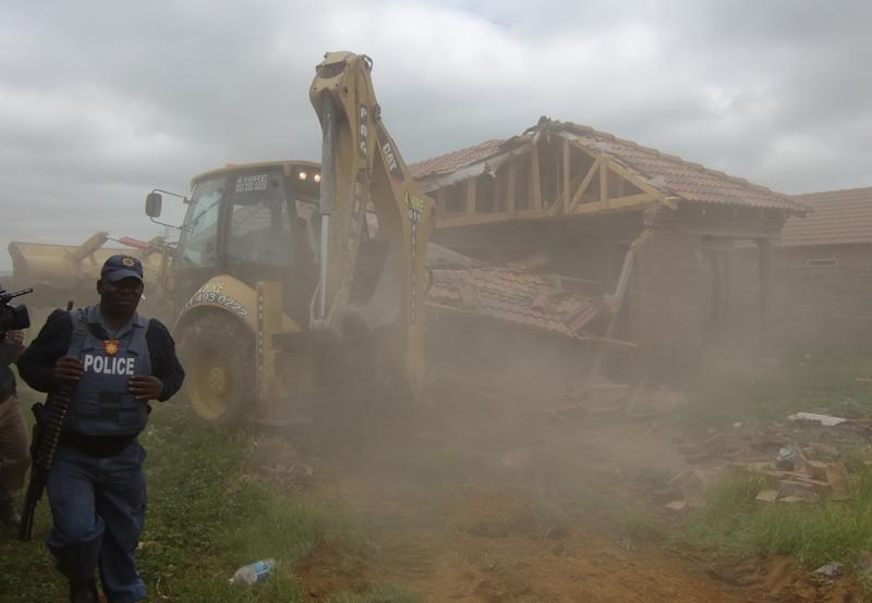 A policeman watches as a bulldozer destroys a home in Lenasia, south of Johannesburg, South Africa, Friday, Nov. 9, 2012. Police supervised the demolition of some 44 homes since last week saying they were constructed on illegally sold land. (AP Photo/Carley Petesch)