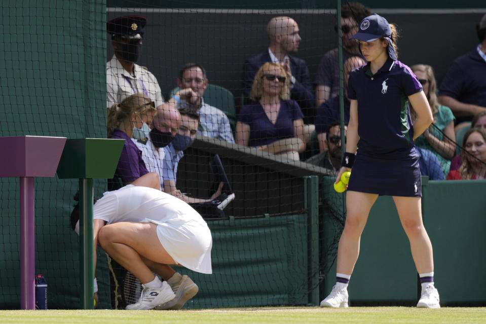 Tunisia's Ons Jabeur vomits ahead of serving for the match during the women's singles third round match against Spain's Garbine Muguruza on day five of the Wimbledon Tennis Championships in London, Friday July 2, 2021. (AP Photo/Kirsty Wigglesworth)