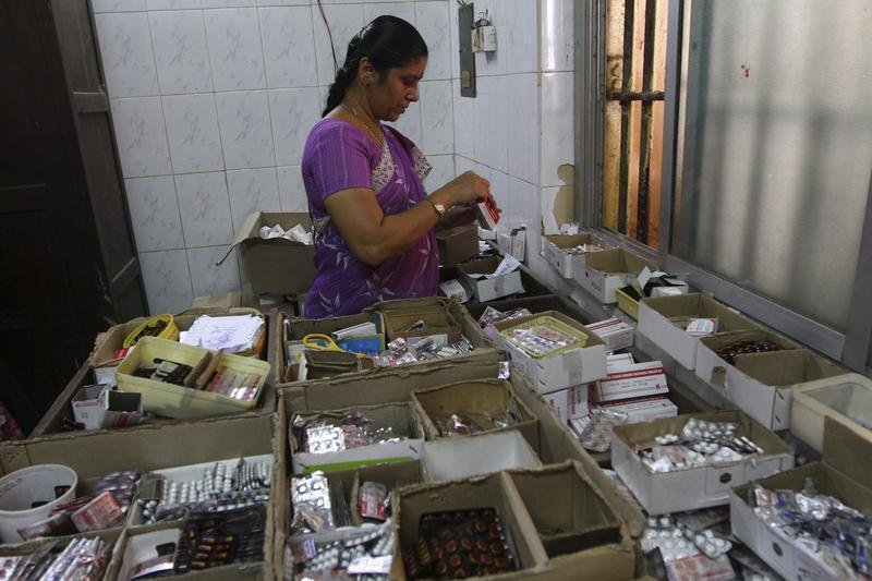 A pharmacists sorts free medication provided by the government, which will be given to patients, at RGGGH in Chenna