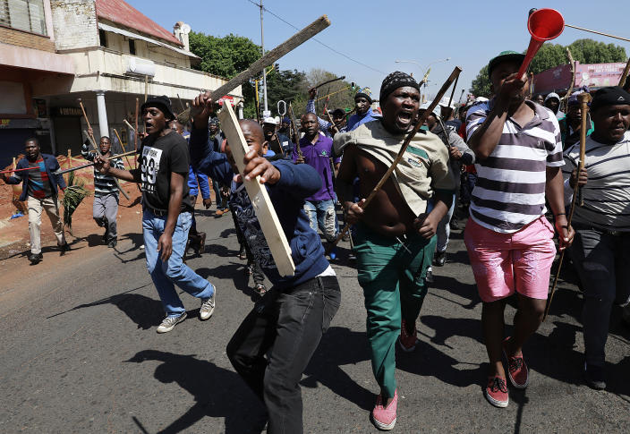 In this photo taken Sunday, Sept. 8, 2019, residents of local hostels march with homemade weapons in Johannesburg. South African police say that two more people have been killed in Johannesburg, bringing to 12 the number of deaths since violence against foreign-owned shops erupted last month. (AP Photo)