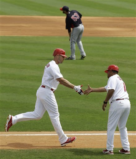 St. Louis Cardinals' Matt Holliday, bottom left, greets third base coach Jose Oquendo as he rounds the bases after hitting a two-run home run off of Minnesota Twins starting pitcher Nick Blackburn (53) in the fourth inning of a spring training baseball game in Jupiter, Fla., Sunday, March 25, 2012. (AP Photo/Patrick Semansky)
