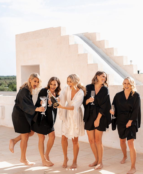 <p>As the gorgeous bride got ready for the day ahead with her four bridesmaids, they indulged in a cheeky glass of Champagne. Anna opted for a white dressing gown while her besties wore contrasting black to make her stand out. Source: Instagram/AnnaHeinrich </p>