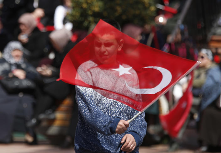 A supporter of Turkey's President Recep Tayyip Erdogan waves a flag at a rally of his ruling Justice and Development Party's (AKP), in Istanbul, Friday, March 29, 2019, ahead of local elections scheduled for March 31, 2019. Erdogan has been holding multiple daily rallies across the country, using highly polarising language, portraying the opposition as traitors who are supported by terrorists, blaming ills on foreign forces and stirring up nationalist and religious sentiments. (AP Photo/Lefteris Pitarakis)