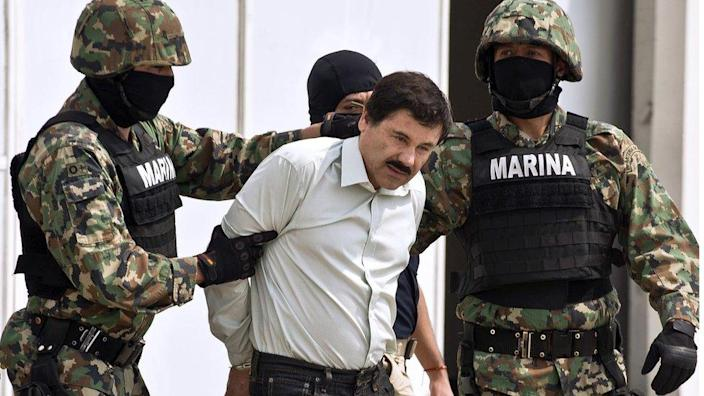 Joaquin El Chapo Guzman is escorted by marines as he is presented to the press on 22 February 2014