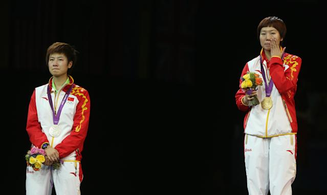 LONDON, ENGLAND - AUGUST 01: Xiaoxia Li of China stands on the podium for her national anthem after winning the Gold medal and Ning Ding of China (L) the Silver following the Women's Singles Table Tennis Gold Medal match on Day 5 of the London 2012 Olympic Games at ExCeL on August 1, 2012 in London, England. (Photo by Feng Li/Getty Images)