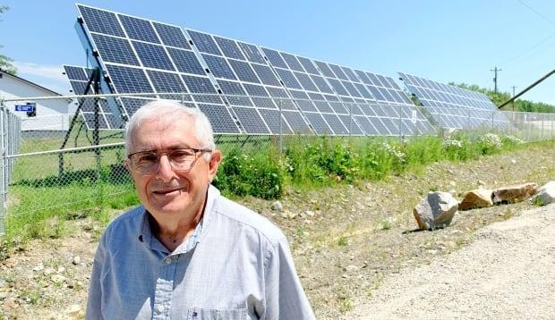 Danny Muise, warden for the Municipality of the District of Argyle, stands beside the solar park that powers the municipality's new net-zero building. (Phlis McGregor/CBC - image credit)