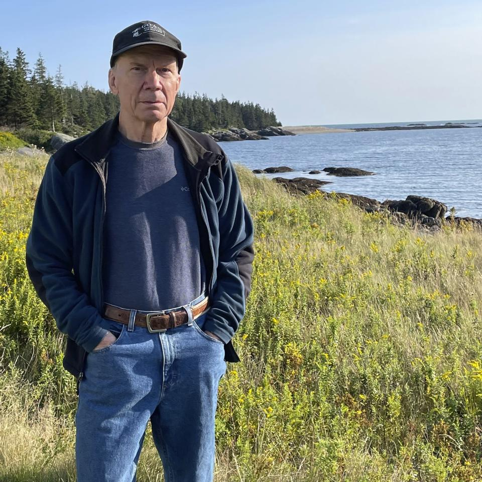In this photo provided by Donna Hopkins, Charlie Hopkins stands near his home along the shoreline of Isle au Haut Maine, on Sept. 4, 2021. The island, which is accessible only by boat, has slow internet service in some locations, including at Hopkins' home. Hopkins has concerns about a U.S. Treasury Department rule that narrows the eligibility for broadband infrastructure spending under the American Rescue Plan, which provides $350 billion of flexible funds to state and local governments. (Donna Hopkins via AP)