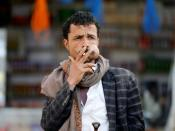 Man smokes a cigarette as he chews qat, a mild stimulant, at a fruit market amid concerns of the spread of the coronavirus disease (COVID-19) in Sanaa