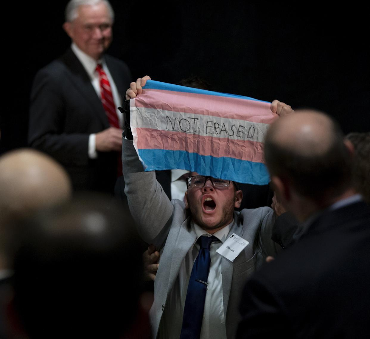 "A third protester held up a transgender pride flag while yelling, ""We will not be erased!"" (Photo: EFE)"
