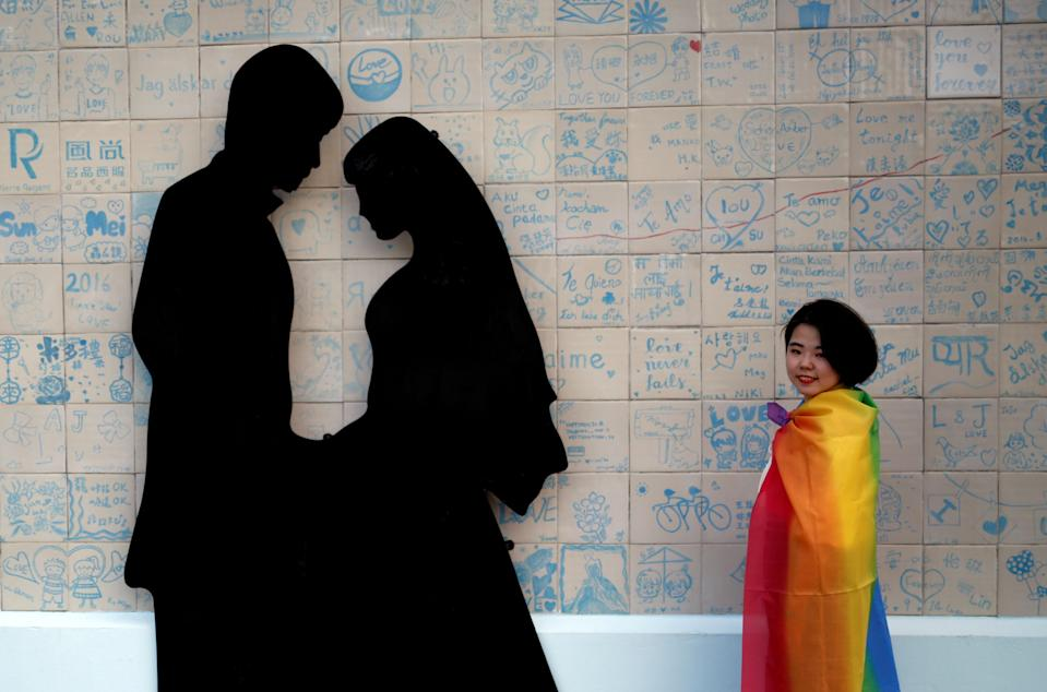 A participant poses next to a wedding studio during a lesbian, gay, bisexual and transgender pride parade to support same-sex marriage in Taipei, Taiwan on 27 October, 2018. (PHOTO: Reuters)