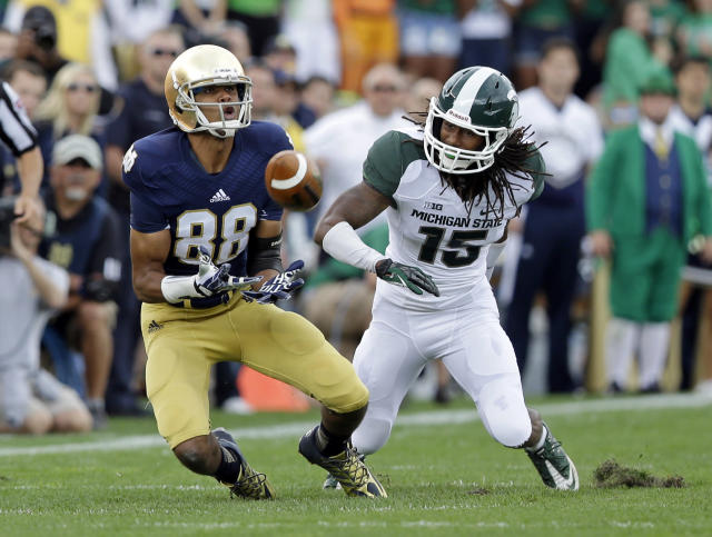 Notre Dame wide receiver Corey Robinson, left, makes a catch in front of Michigan State cornerback Trae Waynes during the first half of an NCAA college football game in South Bend, Ind., Saturday, Sept. 21, 2013. (AP Photo/Michael Conroy)