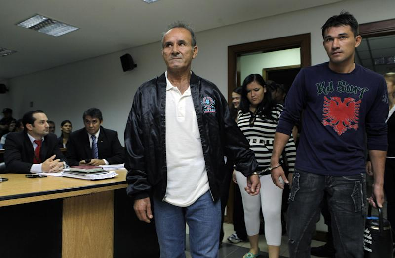 Imprisoned landless farmers Felix Balmori, center, and Adalberto Castro, right, enter the court room handcuffed to each other for their pre-trial hearing in Col. Oviedo city, Paraguay, Thursday, Feb. 14, 2013. The prosecutor says he has no physical evidence showing who killed six police officers during a bloody land dispute that prompted the downfall of Paraguayan President Fernando Lugo. He says he didn't even try to determine who killed 11 farm workers who also died when the bullets started flying. Even so, Jalil Rachid has said he'll ask a judge on Thursday to formally charge 10 peasants who survived the fusillade with attempted homicide, and punish them with up to 25 years in prison. (AP Photo/Jorge Saenz)