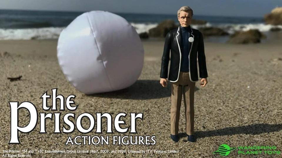 An action figure of The Prisoner's Agent Six on the beach.