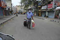 A man with luggage walks looking for transportation during reimposed weekend lockdown to prevent the spread of coronavirus in Jammu, India, Sunday, Aug 2, 2020. India is the third hardest-hit country by the pandemic in the world after the United States and Brazil. (AP Photo/Channi Anand)