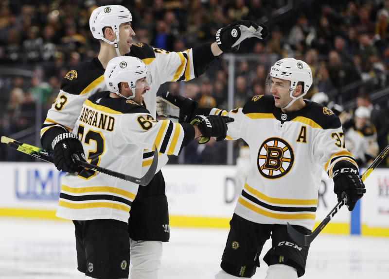 FILE - In this Feb. 20, 2019, file photo, Boston Bruins' Brad Marchand, front, celebrates with teammates Zdenoa Chara, back left, and Patrice Bergeron after scoring against the Vegas Golden Knights during the third period of an NHL hockey game in Las Vegas. The three veterans who hoisted the Stanley Cup after winning it all in 2011 are among the core Bruins who will host the St. Louis Blues Monday, May 27, 2019, in Game 1 of the Stanley Cup Final. (AP Photo/John Locher, File)