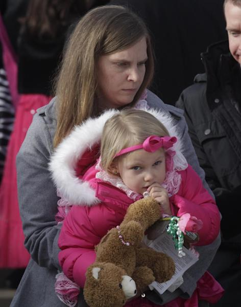 FILE-- in this photo taken on Dec. 22, 2012, Alissa Parker carries her daughter, Samantha, 3, following funeral services for her 6-year old daughter, Emilie, in Ogden, Utah. The moment Alissa Parker learned of a shooting at her daughter's school in Newtown, Conn., she suddenly regretted not pointing out what she had seen as security gaps at Sandy Hook Elementary School. Parker, whose daughter, Emilie, was among 20 first-graders killed in the Dec. 14 massacre, had thought security could have been tighter, although she never could have guessed it would be tested by a gunman with a military-style, semi-automatic rifle. (AP Photo/Rick Bowmer)