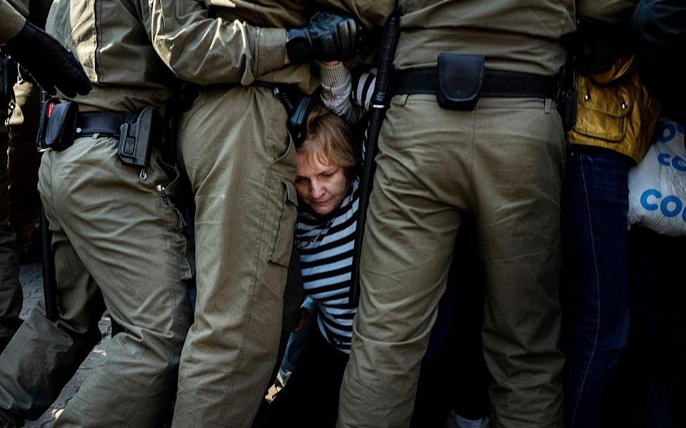 Police officers block and detain protesters during an opposition rally in September 2020 - AP Photo/Misha Friedman