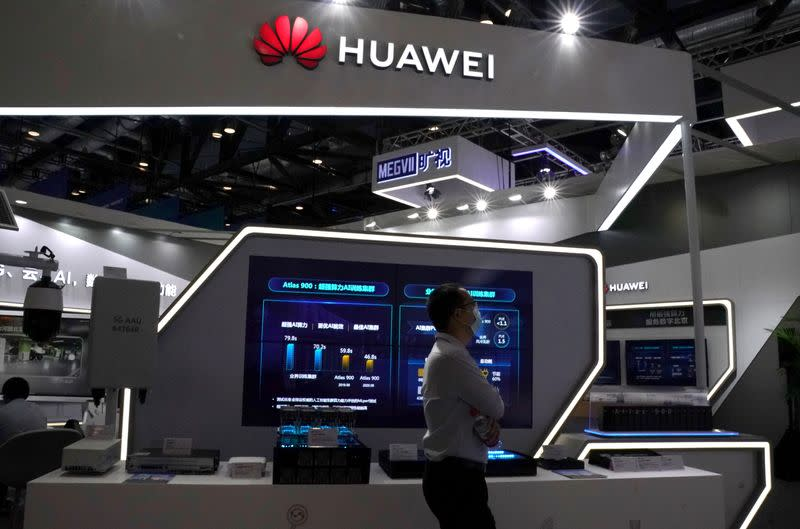 FILE PHOTO: Man wearing a face mask following the coronavirus disease (COVID-19) outbreak walks past a booth of Huawei at the 2020 China International Fair for Trade in Services (CIFTIS) in Beijing
