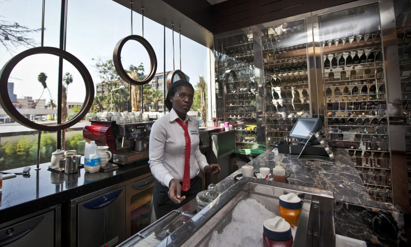 In this photo taken Wednesday, Sept. 26, 2012, a member of staff prepares coffee at the cafe and wine bar of the Sankara Nairobi hotel in Nairobi, Kenya. International hotel developers are planning nearly 40,000 new rooms across Africa in the coming years, the continent's business travel is increasing, and Africa's middle class will soon begin leisure travel en masse. (AP Photo/Ben Curtis)
