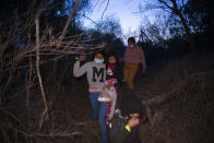 Migrants families, mostly from Central American countries, walk through the brush after being smuggled across the Rio Grande river in Roma, Texas, Wednesday, March 24, 2021. (AP Photo/Dario Lopez-Mills)