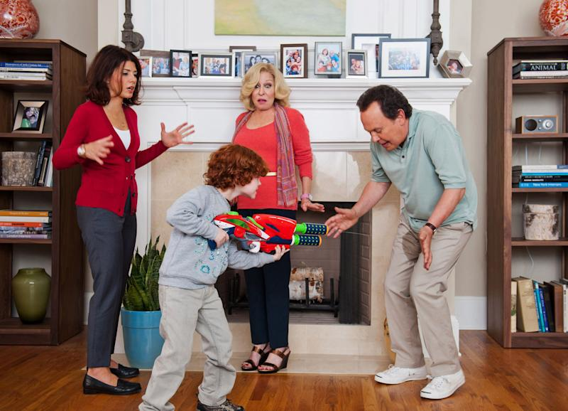 """This undated publicity photo released by Twentieth Century Fox and Walden Media shows Billy Crystal, right, as Artie who reacts to his grandson, Kyle Harrison Breitkopf, center, Barker's water-rifle shenanigans while Marisa Tomei, left, as the mother Alice and Bette Midler as the grandmother, Diane, look on in a scene from the film, """"Parental Guidance."""" (AP Photo/Twentieth Century Fox/Walden Media, Phil Caruso)"""