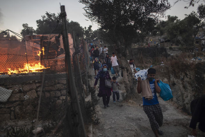 FILE - In this Wednesday, Sept. 9, 2020, file photo, refugees and migrants carrying their belongings flee a fire burning at Moria camp, on Lesbos island, Greece. Greece's notoriously squalid refugee camp of Moria burnt down last September on the island of Lesbos. It left around 12,000 people in need of emergency housing as winter approached. European leaders then vowed such squalid facilities would be a thing of the past. But aid agencies say that a year later the conditions for asylum seekers on the eastern Greek islands have barely improved.(AP Photo/Petros Giannakouris, File)