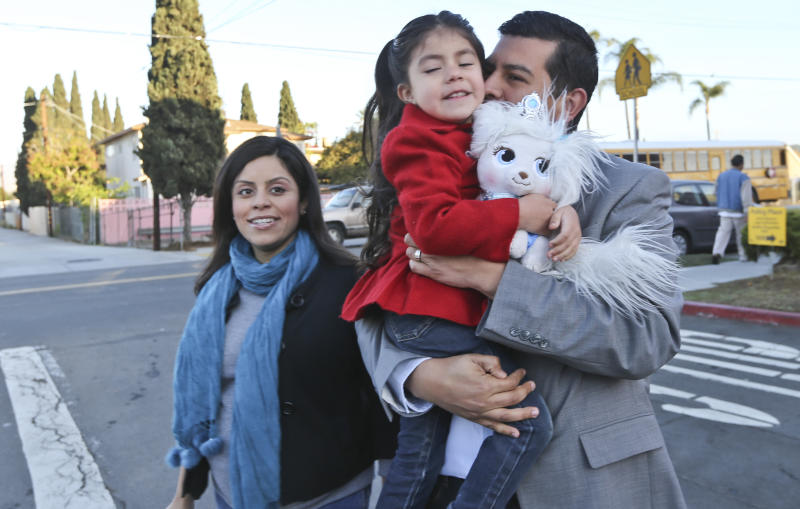 San Diego mayoral candidate David Alvarez, carries his daughter, Izel, as he and his wife, Xochitl, arrive at a polling location in the Logan Heights neighborhood where Alvarez grew up and still lives Tuesday, Feb. 11, 2014 in San Diego. (AP Photo/Lenny Ignelzi)