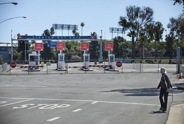 """A pedestrian looks at an entrance to Dodger Stadium that is closed on what would have been opening day if not for the coronavirus outbreak. <span class=""""copyright"""">(Mel Melcon / Los Angeles Times)</span>"""