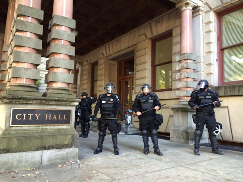 FILE - In this Oct. 12, 2016, file photo, Portland police stand guard outside of City Hall in Portland, Ore., after protestors disrupted a city council meeting, leading to arrests. The City Council approved an emergency ordinance Wednesday, March 15, 2017, that would allow the city to eject disruptive protesters and ban them from council chambers for up to 60 days in some cases. (Brad Schmidt/The Oregonian via AP, File)