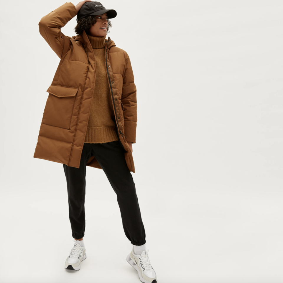 model wearing black pants, white sneakers, and camel coloured Everlane The ReNew Long Puffer