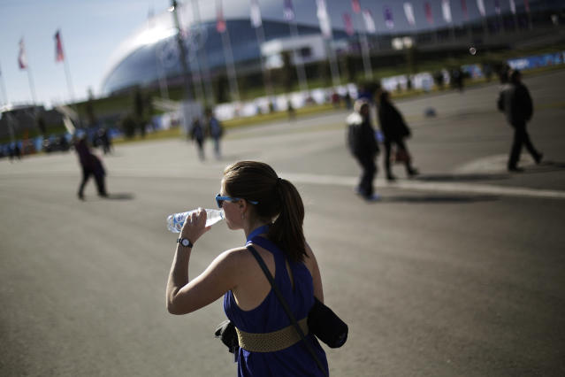Kaylee Weil, of San Diego, Calif., takes a drink of water while walking through the Olympic Park wearing a sun dress at the 2014 Winter Olympics, Wednesday, Feb. 12, 2014, in Sochi, Russia. Temperatures are predicted near 60 degrees Fahrenheit in Sochi on Wednesday. (AP Photo/David Goldman)