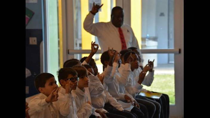 Holmes Elementary School math teacher Abe Coleman in class with the students he had mentored as part of his leadership role with the 5000 Role Models of Excellence Program at the Liberty City School.