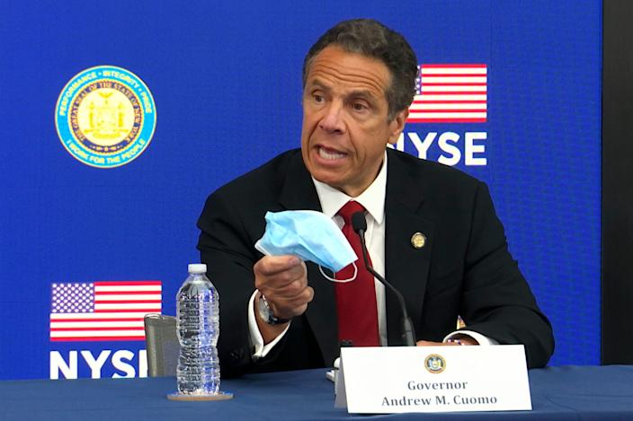 New York Gov, Andrew Cuomo holds his face mask while talking to the media at the New York Stock Exchange, Tuesday, March 26, 2020. Gov. Cuomo rang the opening bell as the trading floor partially reopened during the coronavirus pandemic.