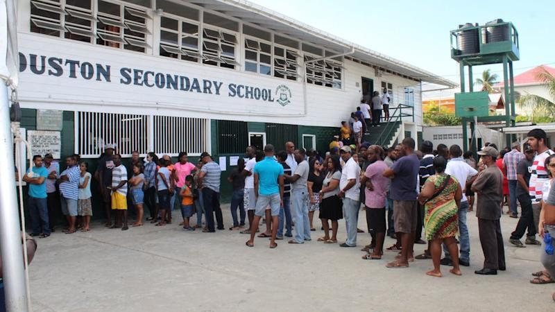 People in Georgetown, Guyana, wait in a queue to cast their vote