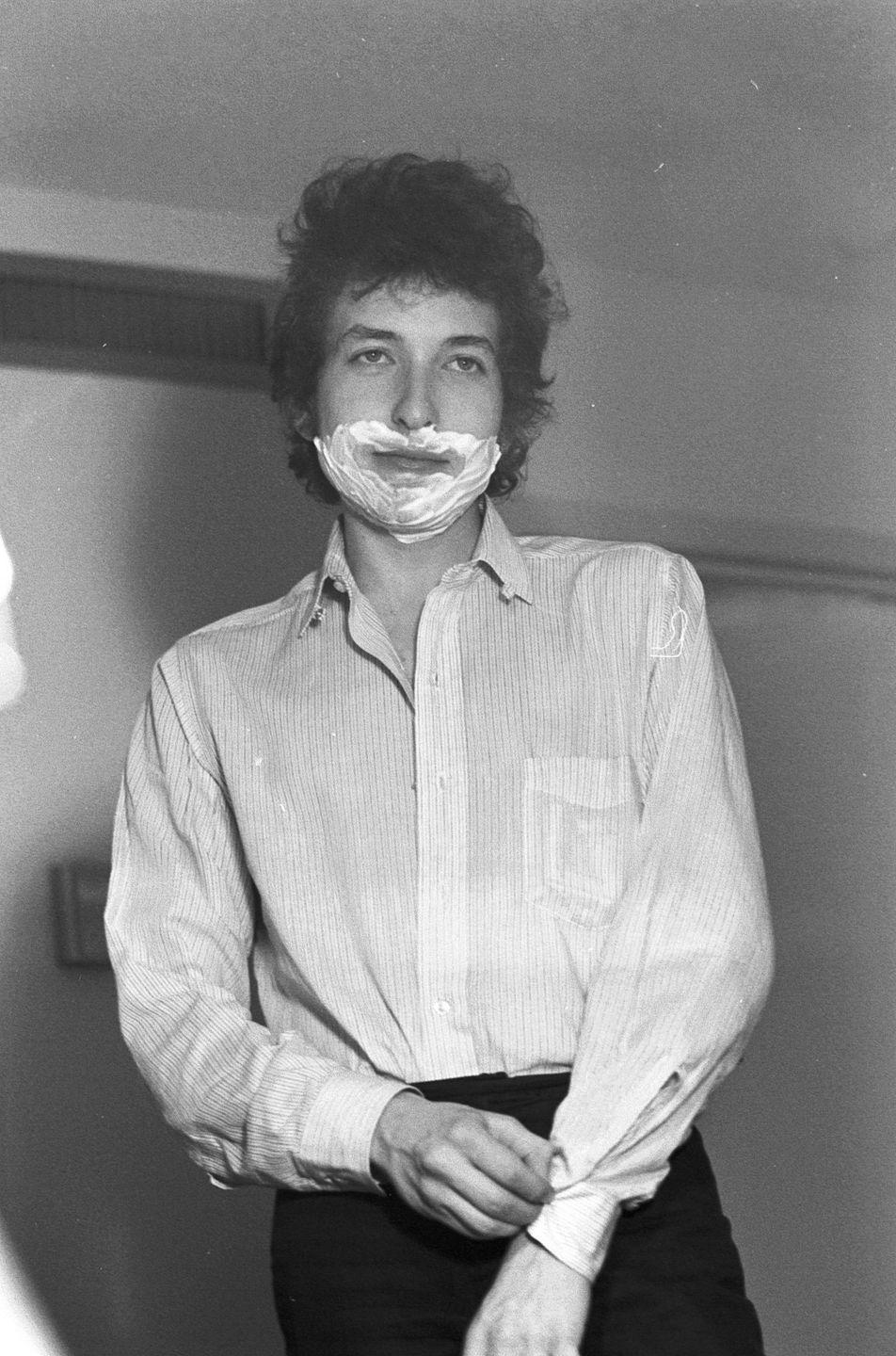 <p>Bob Dylan with shaving cream on his face, backstage at an unknown venue, 1964.</p>